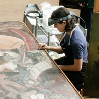 Seated student cleaning painting