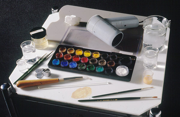 tools for tempera retouching, including dry pigments, brushes, burnishing tool, egg tempera, and synthetic varnish